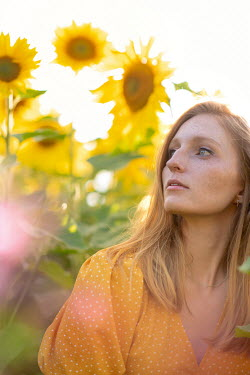 Rebecca Knowles Young woman in sunflower field