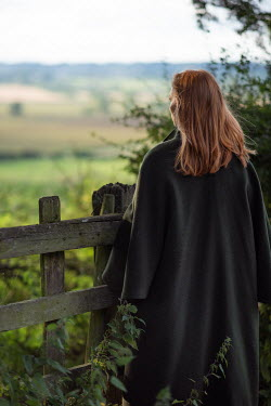 Rebecca Knowles Young woman in coat standing at fence