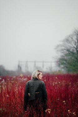 Angela Ward-Brown Young woman in black leather jacket standing in red field