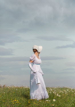 Joanna Czogala Young woman in white dress and bonnet standing in field