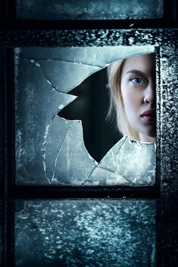Magdalena Russocka woman staring through  hole in broken window
