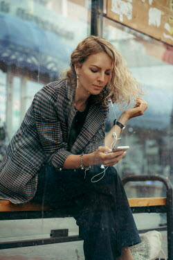 Maria Yakimova Woman with smart phone at bus stop