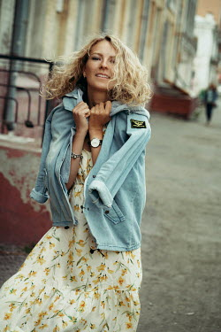 Maria Yakimova Woman in denim jacket and floral dress