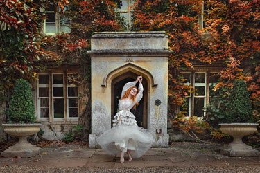 Rebecca Knowles Young woman in white dress dancing by arch