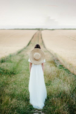 Angela Ward-Brown Young woman in white dress and straw hat standing in field