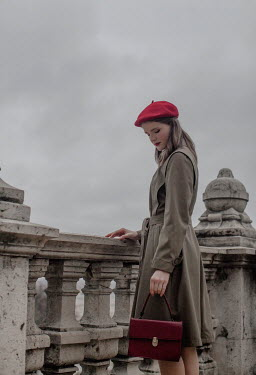 Nikaa Young woman in red beret and coat standing by stone balustrade