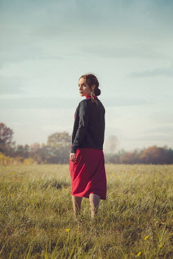 Joanna Czogala Young woman in 1940s red dress standing in field