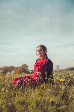 Joanna Czogala Young woman in 1940s red dress sitting in field