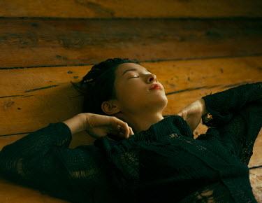 Maria Yakimova ASIAN WOMAN LYING ON FLOORBOARDS DREAMING Women