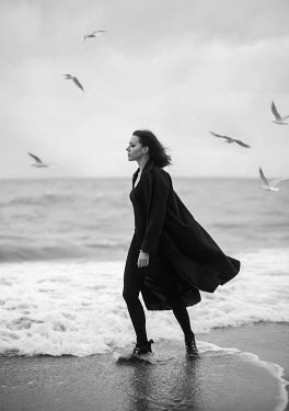 Elena Alferova WOMAN WITH COAT PADDLING IN SEA Women