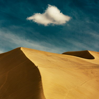 David Keochkerian DISTANT MAN ON SAND DUNE WITH CLOUD Desert