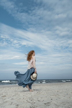 Magdalena Russocka woman holding hat walking on beach