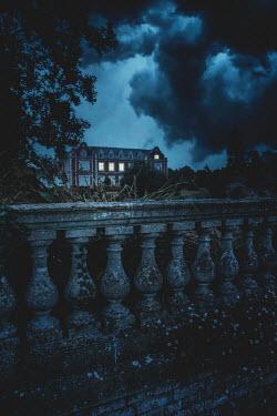 Nic Skerten Mansion under storm clouds at night