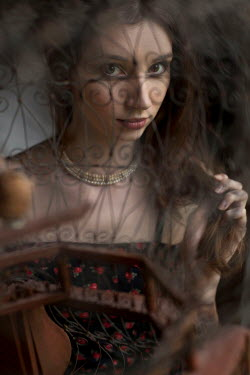 Allan Jenkins Young woman behind wrought iron