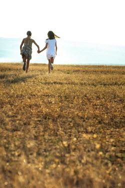 Galya Ivanova Teenage girls holding hands and running in field
