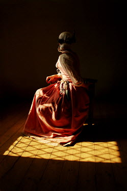 John Foley Young woman in pink dress sitting in shadow