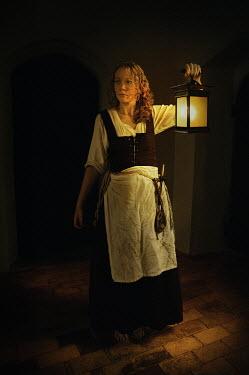 John Foley Woman in historic dress holding lantern