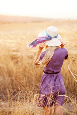 Kerstin Marinov Young woman with purple dress and sun hat in field