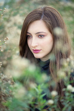 Mohamad Itani Young woman with pink lipstick behind branches