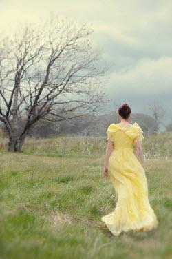Susan Fox Young woman in yellow dress walking in field
