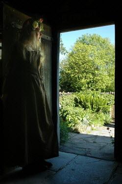 John Foley Historic woman with flower crown standing in doorway