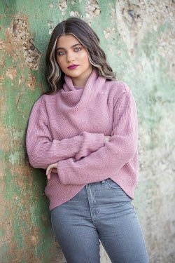Mohamad Itani Young woman in pink sweater leaning on wall