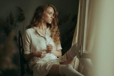 Maria Yakimova Young woman in white dress sitting by window