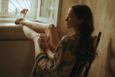 Maria Yakimova Young woman with feet up on windowsill