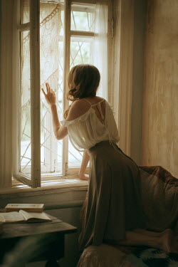 Maria Yakimova Young woman looking through window