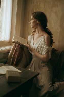 Maria Yakimova Young woman holding book by window