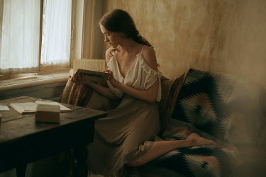 Maria Yakimova Young woman reading book by window