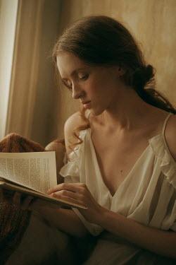Maria Yakimova Young woman reading book by window