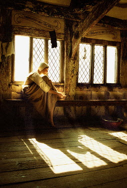 John Foley MEDIEVAL WOMAN SITTING INDOORS IN SUNLIGHT Women