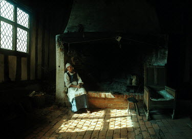 John Foley MEDIEVAL WOMAN SITTING BY HEARTH IN HOUSE Women