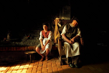 John Foley MEDIEVAL MAN AND BOY SITTING BY FIRE Old People