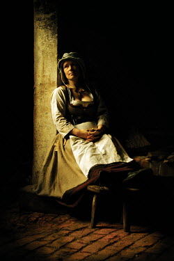 John Foley MEDIEVAL WOMAN SITTING IN SHADOW INDOORS Women