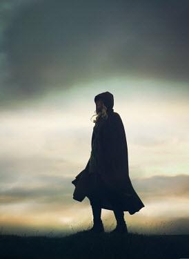 Mark Owen WOMAN IN CAPE WALKING IN WINDY COUNTRYSIDE Women