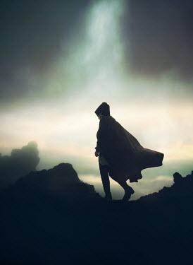 Mark Owen WOMAN IN CAPE WALKING ON HILL AT DUSK Women