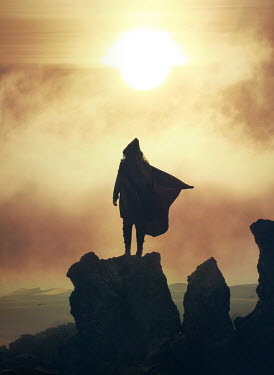 Mark Owen WOMAN WITH CAPE ON ROCKS AT SUNSET Women