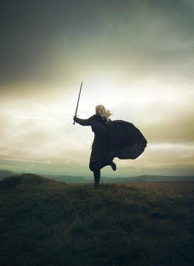 Mark Owen WOMAN RUNNING WITH SWORD IN LANDSCAPE AT DUSK Women