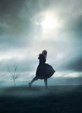 Mark Owen WOMAN IN CAPE RUNNING IN FOGGY COUNTRYSIDE Women