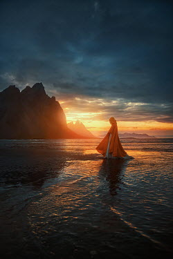 Terrence Drysdale WOMAN IN CAPE ON BEACH WITH MOUNTAINS AT SUNSET Women