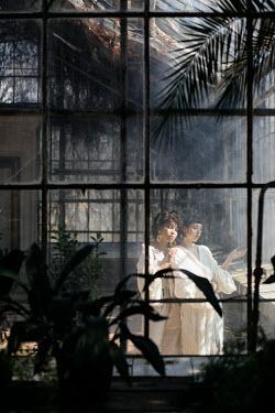 Marta Syrko TWO WOMEN STANDING IN LARGE GREENHOUSE Women
