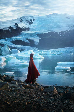 Terrence Drysdale WOMAN IN CAPE BY ICY WATER AND SNOWY MOUNTAINS Women