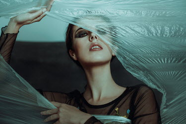 Alisa Andrei WOMAN TEARING HOLE IN PLASTIC SHEET Women