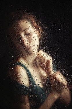 Natasza Fiedotjew woman with closed eyes behind wet window glass