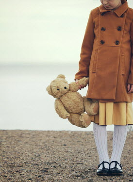 Mark Owen LITTLE GIRL CARRYING TEDDY BEAR ON BEACH Children