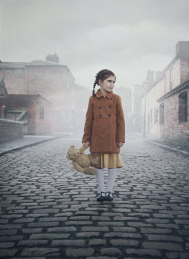 Mark Owen LITTLE GIRL CARRYING TEDDY ON COBBLED STREET Children