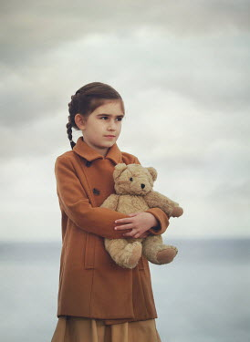 Mark Owen LITTLE GIRL HUGGING TEDDY BEAR ON BEACH Children