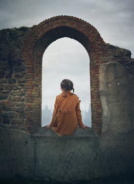 Mark Owen LITTLE GIRL SITTING IN WINDOW OF RUINED BUILDING Children